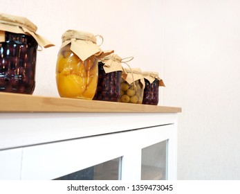 glass jars with canned peaches cherries and spreads wrapped in craft paper and flagella. white buffet.