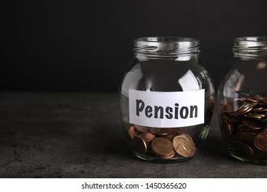 Glass jars with coins and label PENSION on dark table. Space for text