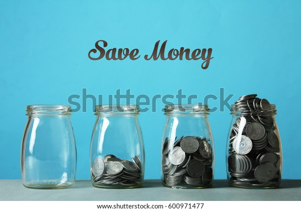Glass jars with coins on a table on a blue background