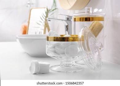 Glass jars with cotton pads and loofahs on table in bathroom