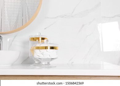 Glass jars with cotton pads and loofahs on table in bathroom. Space for text