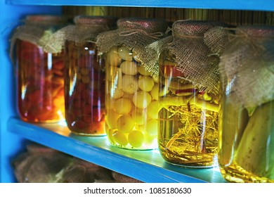 Glass jars covered with burlap fabric with different homemade canned food, preserved vegetables on blue wooden shelves