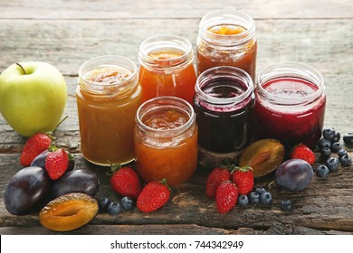 Glass jars with different kinds of jam on wooden table