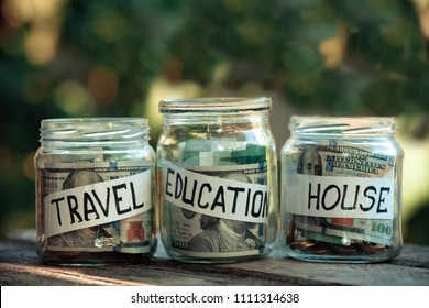 Glass jars with dollars and text: house, travel, education.