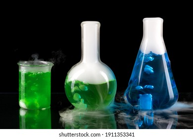 Glass jars with green and blue chemicals.  Sublimation of dry ice on a dark background. Beaker, erlenmeyer flask and boiling flask on the lab table.