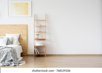 Glass jars on shelves against white wall with copy space in simple bedroom with gold painting above bed