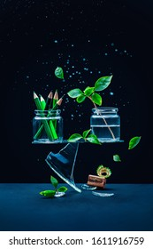 Glass jars with pencils and plants balancing on a shard, art vs nature concept