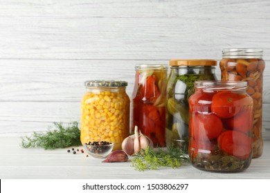 Glass jars with pickled vegetables on white table against wooden background