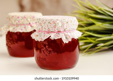 Glass jars of red currant jelly , marmalades on white table. Preserved berries, homemade jam. Copy space