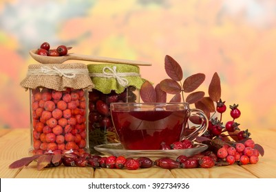 In glass jars rosehip berries, mountain ash and a cup of tea on a background of autumn leaves.