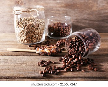 Glass jars and spoon with coffee beans on wooden table on wooden  background
