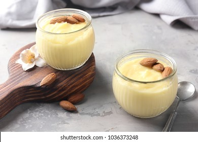 Glass jars with vanilla pudding with almond on table