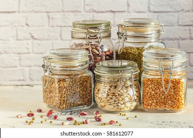 Glass jars with various legumes - beans, mung bean, peas and lentils. Cooking, diet, vegan and vegetarian food.