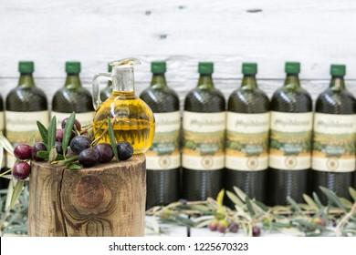 A glass jug and black olives with leaves, bottles of defocused olive oil.