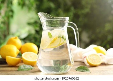 Glass jug of cold lemonade on wooden table