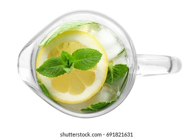 Glass jug of cold lemonade on white background