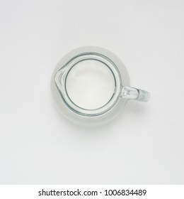 glass jug with milk on white background, top view