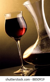 a glass and a jug with red wine