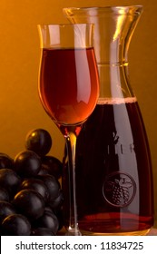 a glass and a jug of red wine and grape