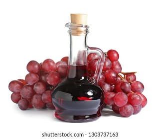 Glass jug with wine vinegar and fresh grapes on white background
