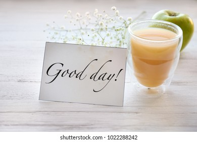 """Glass of juice for breakfast and card with words """"Good day"""" on table"""