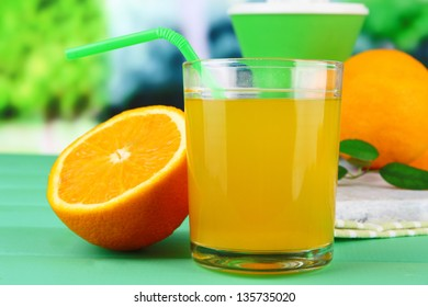 Glass of juice, citrus press and ripe orange on green wooden table