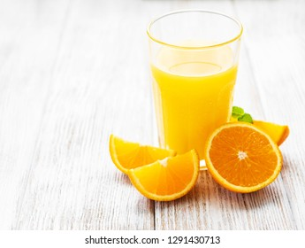 Glass of juice and orange  fruits on a wooden table