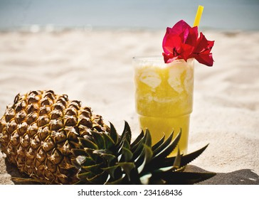 Glass of juice and pineapple on the beach on the tropical island of Bali, Indonesia