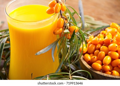 a glass of juice of sea buckthorn and fresh berries on the branch