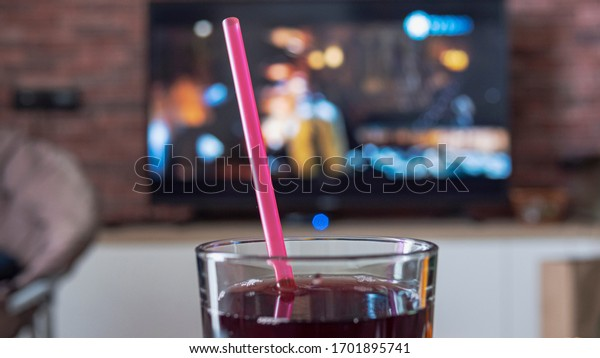 Glass of juice with a straw, in the background TV with the film on. Color bright lighting. Relax and rest at home. Close up of a glass of coke with a tube