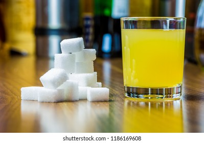 a glass of juice and a lot of sugar cubes are on a table