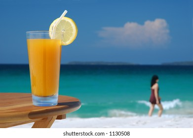 Glass of Juice and Walking Woman Against Tropical Sea