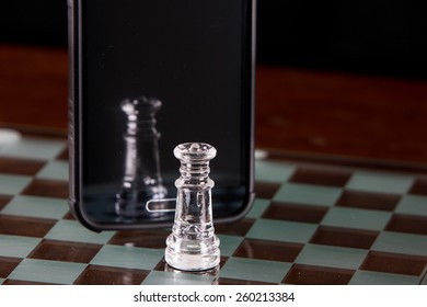 Glass king chess piece with reflection shown in a smart phone.
