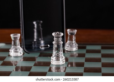 Glass king chess piece with reflection shown in a smart phone.  Pawn pieces are on each side of the phone.