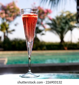 Glass of Kir Royal on the glass table in outdoor resort bar