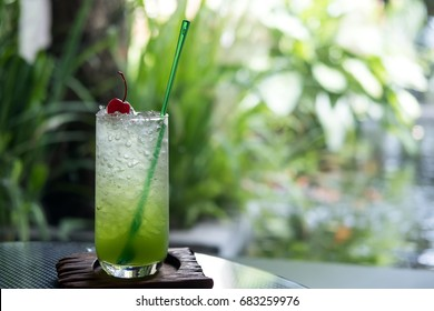 A glass of kiwi italian soda on a wooden saucer in cafe with green nature background