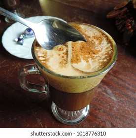 A glass of kogel-mogel coffee with powdered cinnamon - coffee with beaten egg yolk with sugar. Top view, close-up