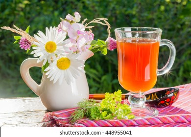 Glass of kvass with a bouquet of wildflowers in a jar on a wooden table in the garden