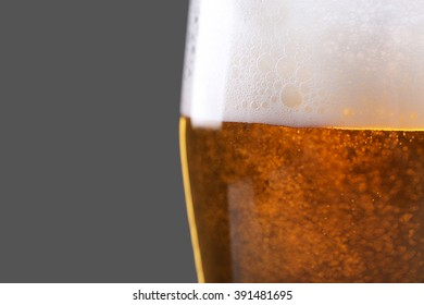 Glass of lager beer on grey background, close up