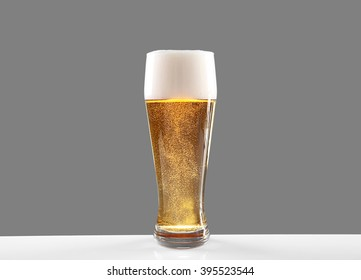 Glass of lager beer on grey background