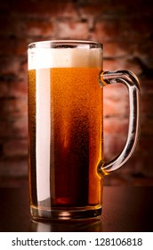 glass of lager on table against brick wall