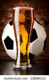 glass of lager with soccer ball on table against brick wall