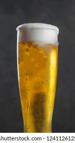 Glass of lager wheat beer with foam.