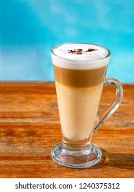 Glass of latte coffee drink on wooden table with defocus blue water of pool background.
