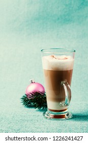 Glass of latte macchiato with caramel syrup, christmas decoration on the background