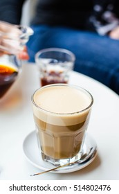 A glass of latte on a white table. In the background somebody pours black coffee.