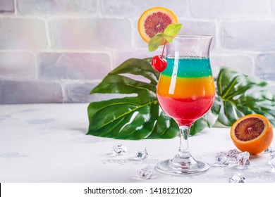 Glass of layered rainbow summer cocktail decorated with cherry and slice of red orange. Exotic summer drink. Copy space