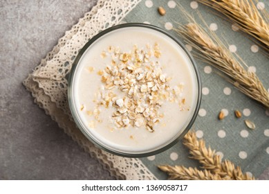 A glass of lean oatmeal milk on a stone background. vegetarian and organic drink food. top view.