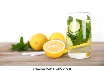 a glass of lemon cucumber water and fresh lemon fruit