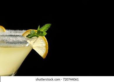 Glass of lemon drop martini with slice of fruit on black background